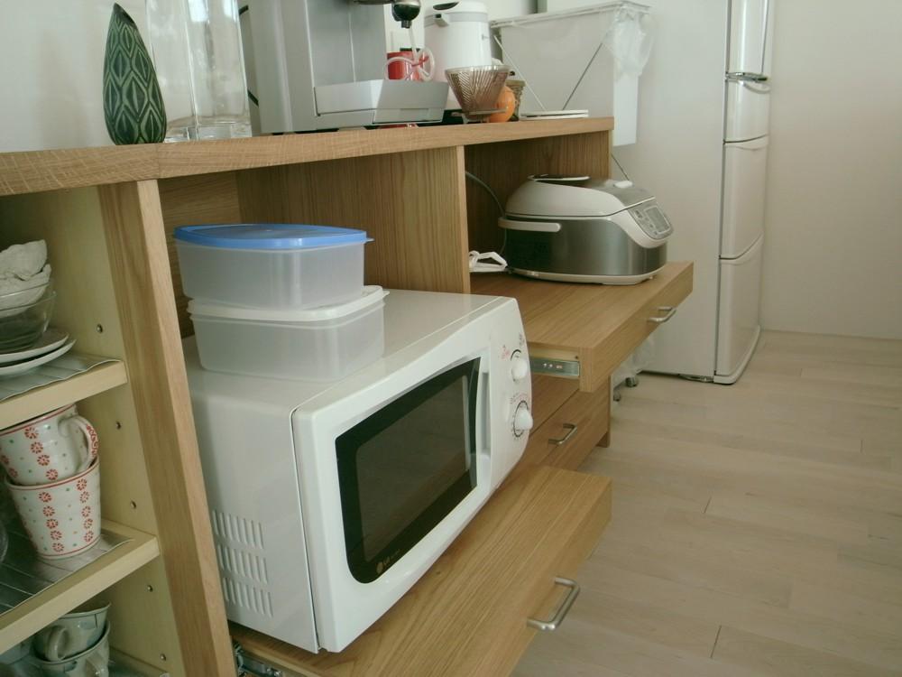 オークのペニンシュラタイプのキッチンと、引戸のあるバックカウンター