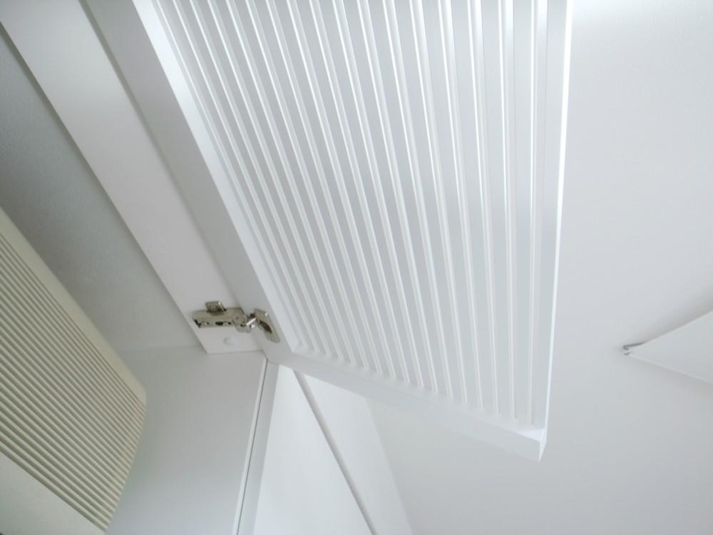 エアコンを隠すルーバーのある白い吊戸棚