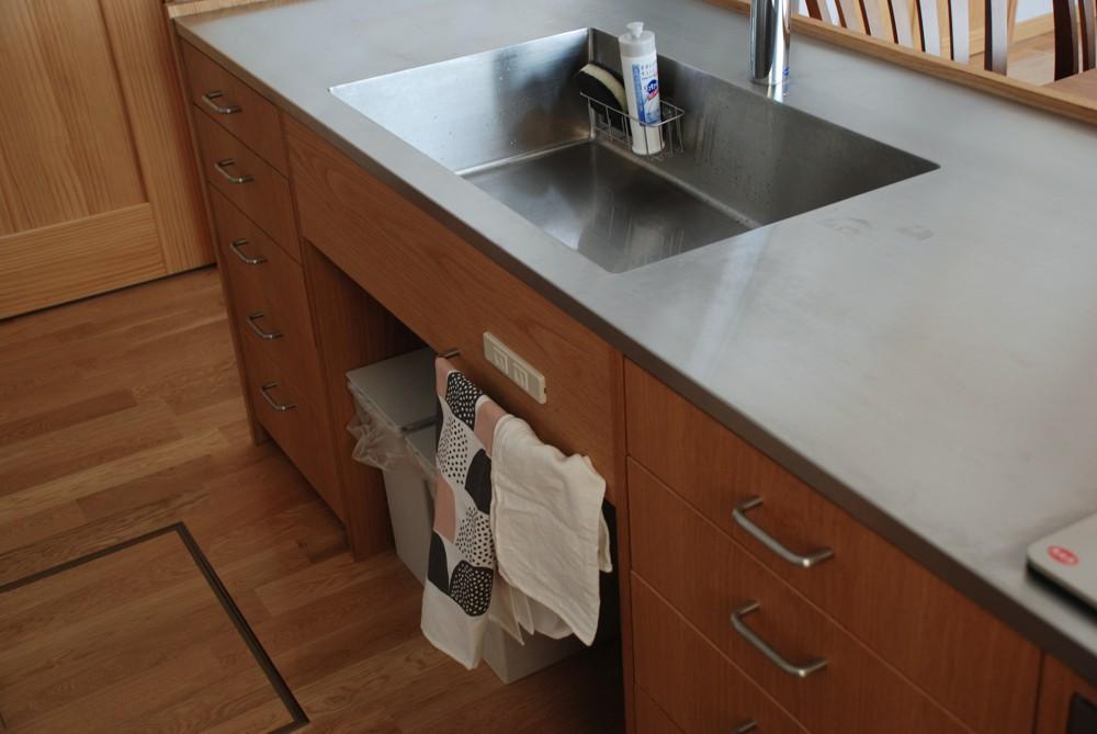 ナラとステンレスのペニンシュラキッチンと引き戸のあるカップボード