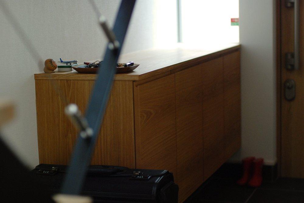 ステンレスカウンターや格子のエアコンパネルのあるタモのモダンな家具