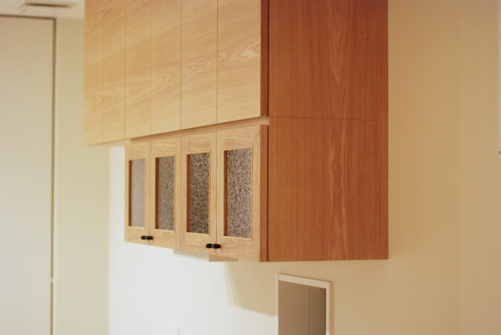 キッチンとダイニングをつなぐタモのバックカウンターと吊戸棚