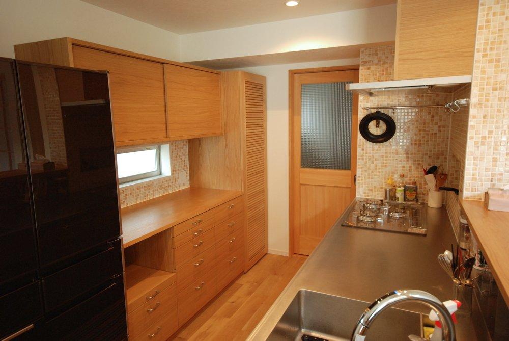 ナラのとバイブレーションカウンターのキッチンと引き戸と格子扉の食器棚