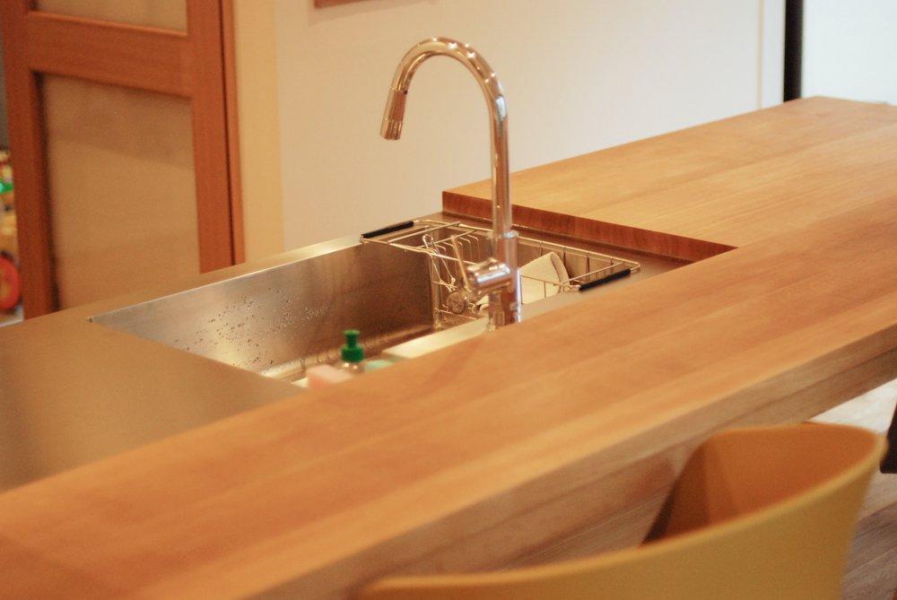 ナラのダイニングテーブルとキッチンが一体になった空間