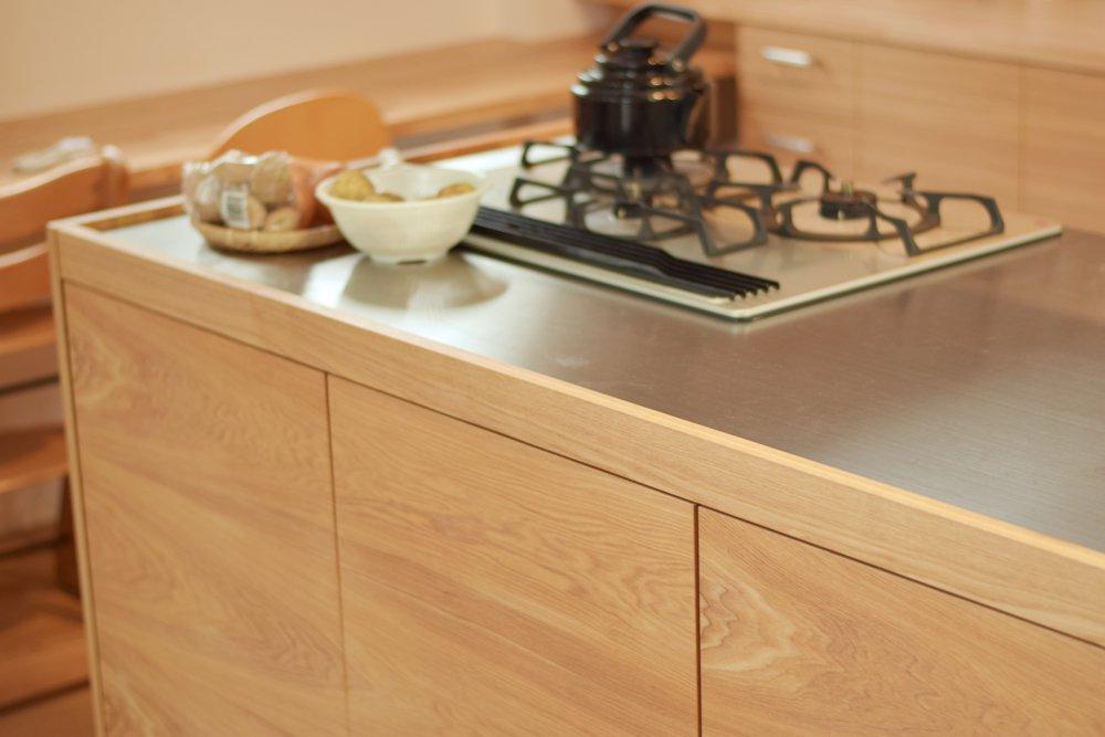 ステンレスとオークの段付きシンクのあるモダンなアイランドキッチン