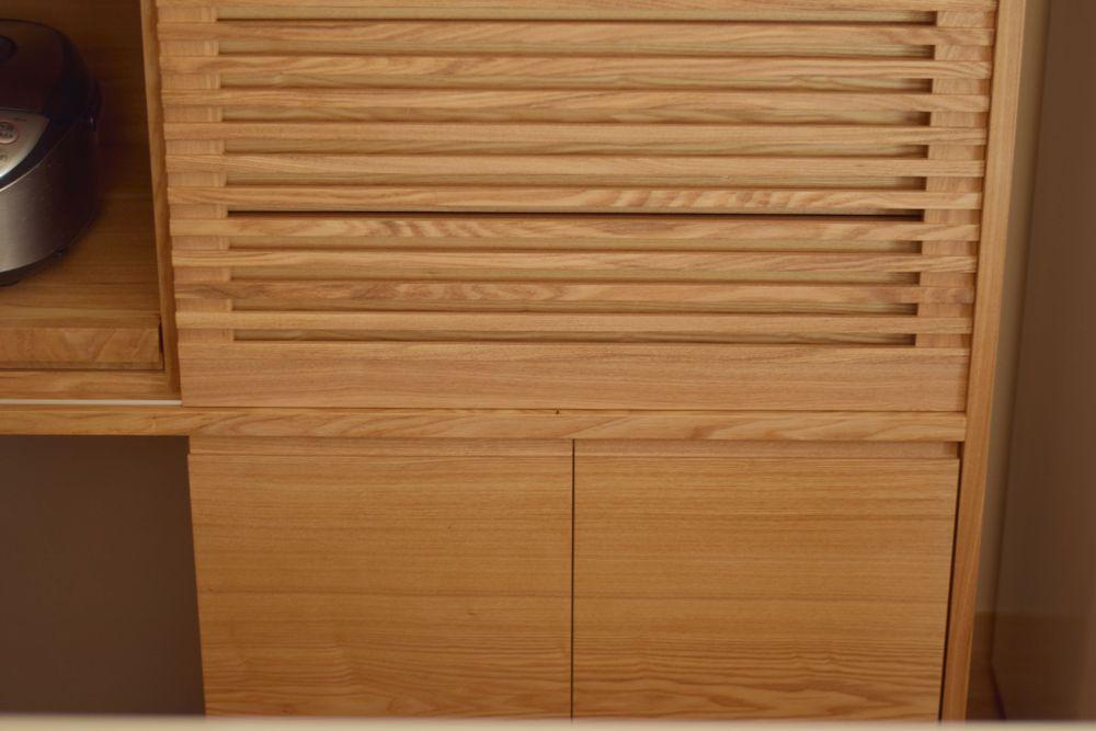 タモを使った和風な印象のカウンター下収納と格子の引き戸のある食器棚