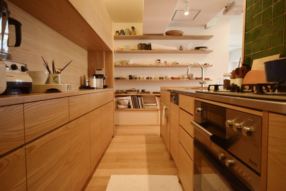 ナラとステンレスのペニンシュラタイプのキッチンと間仕切り食器収納