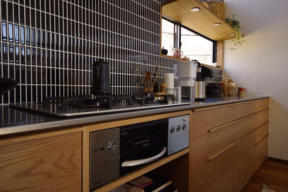 タイルをアルテック柄に貼った壁面とコンロ側のオーダーキッチンキャビネット