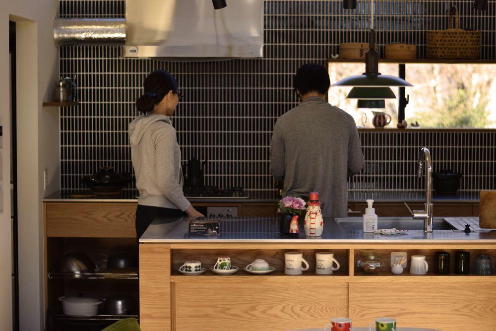 宙に浮いたようなステンレスカウンターのあるオーク材を使ったオーダーキッチン