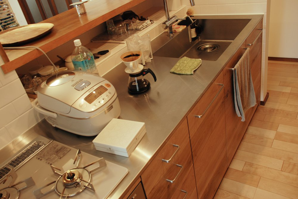 節アリナラ材とステンレスヘアライントップのキッチン