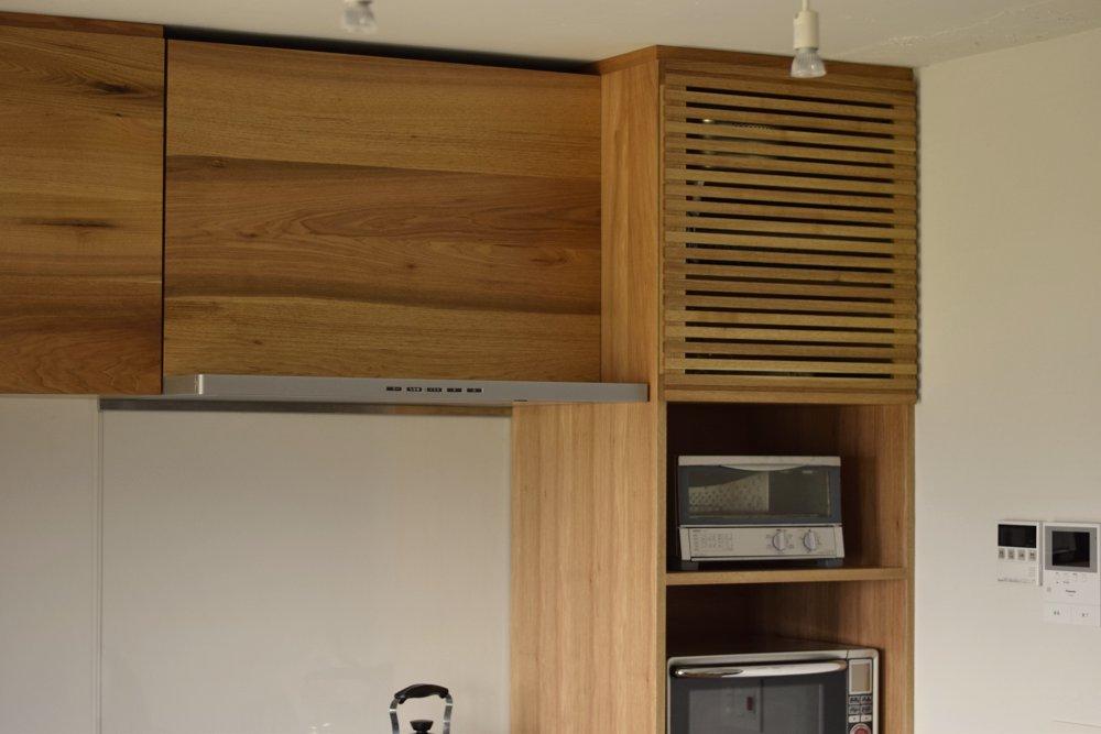格子扉のある吊戸棚とレンジフード幕板