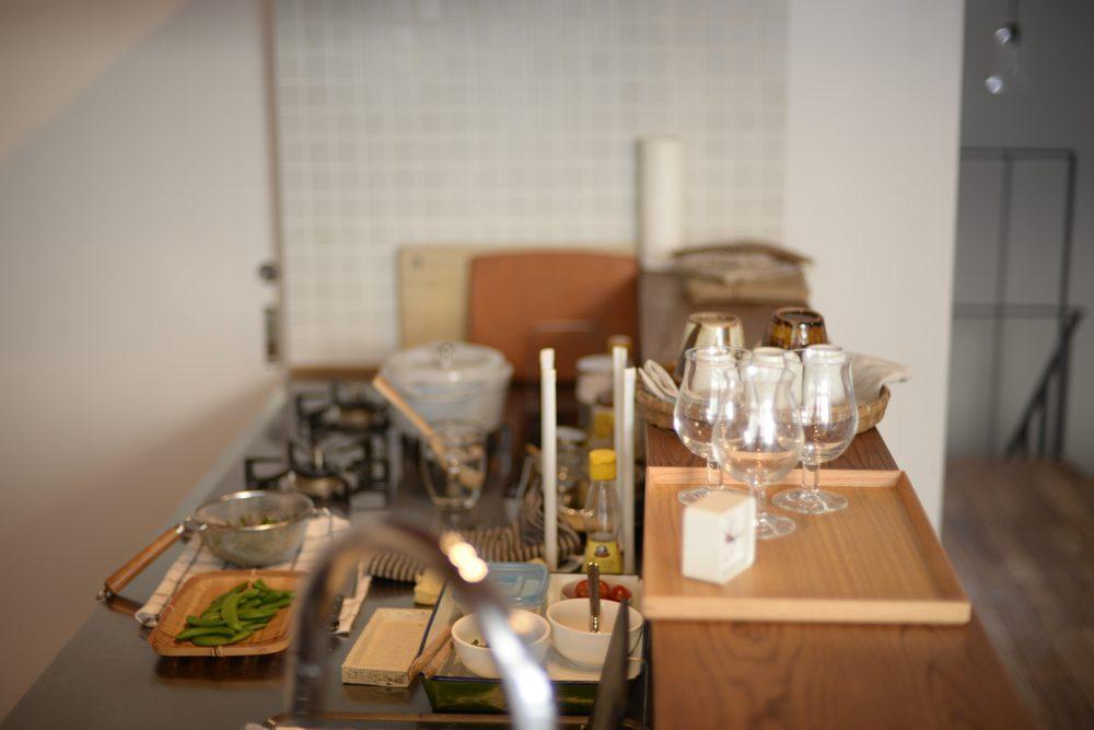 節のあるナラ材と白い化粧板とステンレスのペニンシュラキッチン