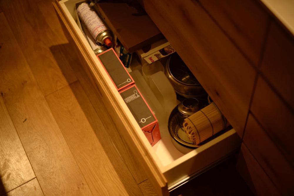 ナラ節アリ材とステンレスを使った壁付けオーダーキッチンとアイランド食器棚